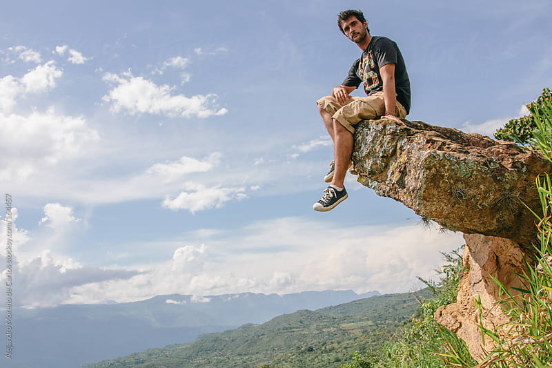Man sitting on a rock with his feet dangling off the edge on nature landscape. Adventure travel by Alejandro Moreno de Carlos for Stocksy United
