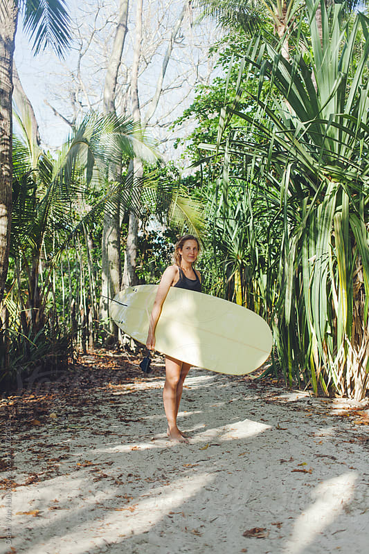 Heathy woman holding her surfboard on her way to the beach to go surfing. by Denni Van Huis for Stocksy United