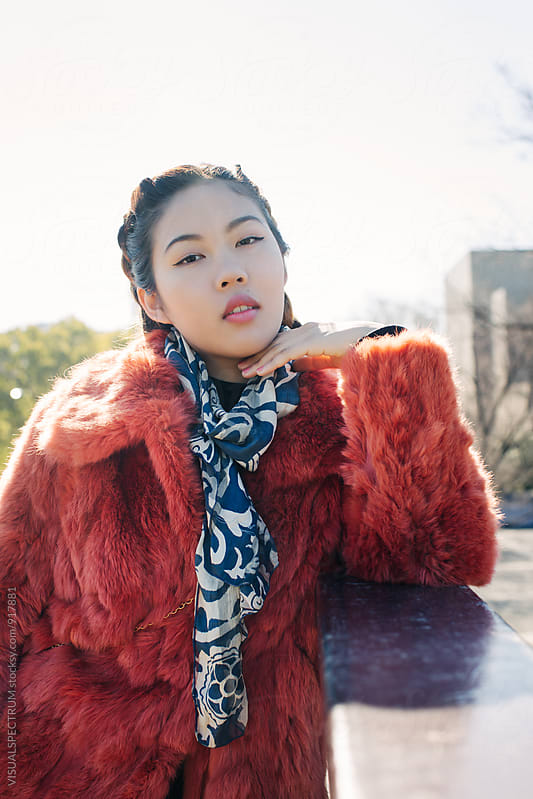 Sunny Outdoor Portrait of Young Pretty Asian Girl in Red Fur Coat by VISUALSPECTRUM for Stocksy United