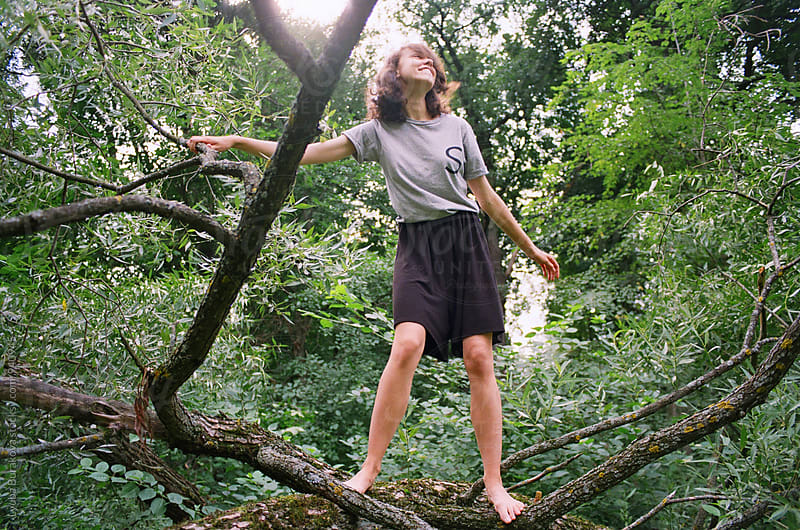 Happy young woman on a tree  by Lyuba Burakova for Stocksy United