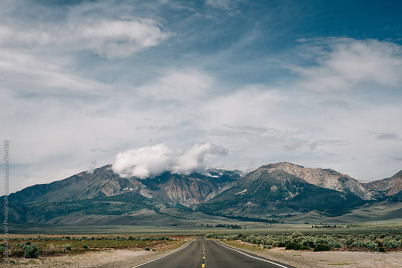 Highway leading to mountains by Isaiah & Taylor Photography for Stocksy United
