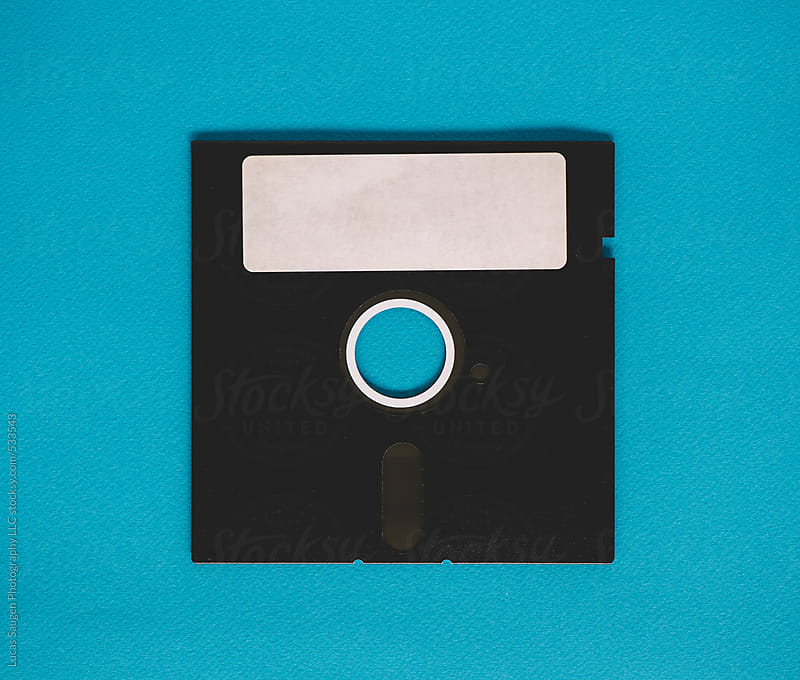 Old floppy disk sitting on a blue background. by Lucas Saugen for Stocksy United