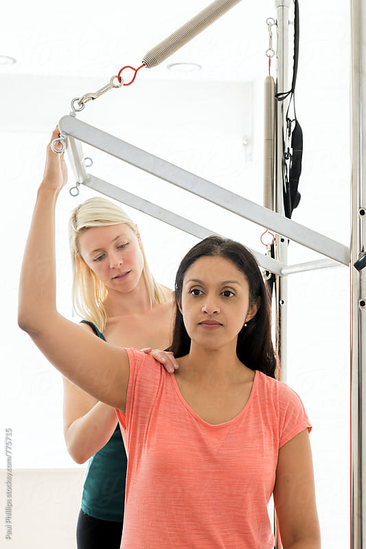 Pilates instructor guiding a student through exercise using the Trapeze or  Cadillac by Paul Phillips for Stocksy United