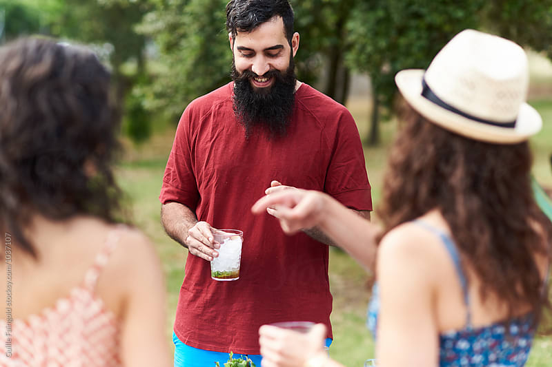 Portrait of smiling bearded man with drink talking to his unfocused friends by Guille Faingold for Stocksy United