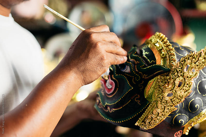 Artisan painting 'Hua Khon' traditional mask for Thai performing arts by Nabi Tang for Stocksy United