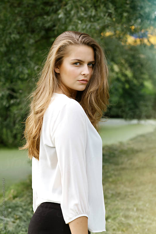 beautiful young woman in white shirt looking over her shoulder by Rene de Haan for Stocksy United