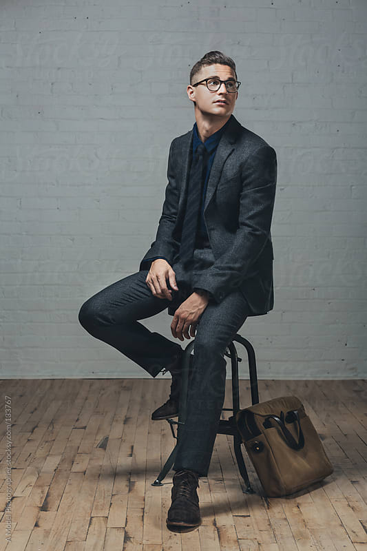 A well dressed man sitting on a stool looking up by Ania Boniecka for Stocksy United