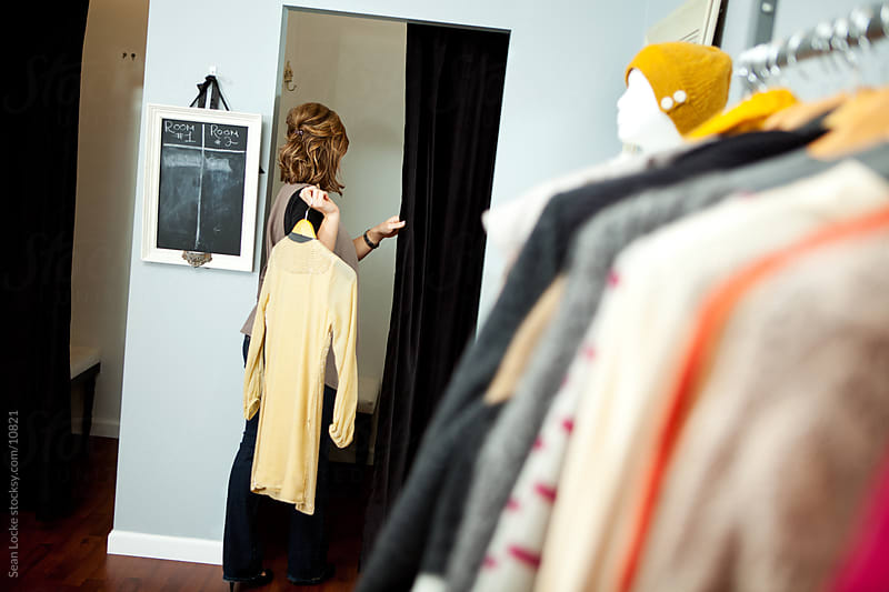 Boutique: Woman Going Into Dressing Room with Clothing by Sean Locke for Stocksy United