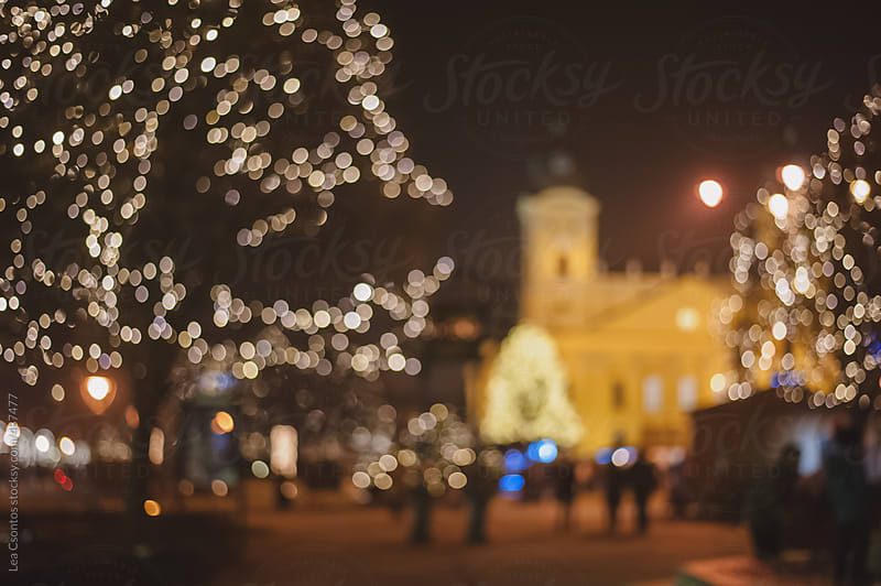 Out of focus christmas lights in a city by Lea Csontos for Stocksy United