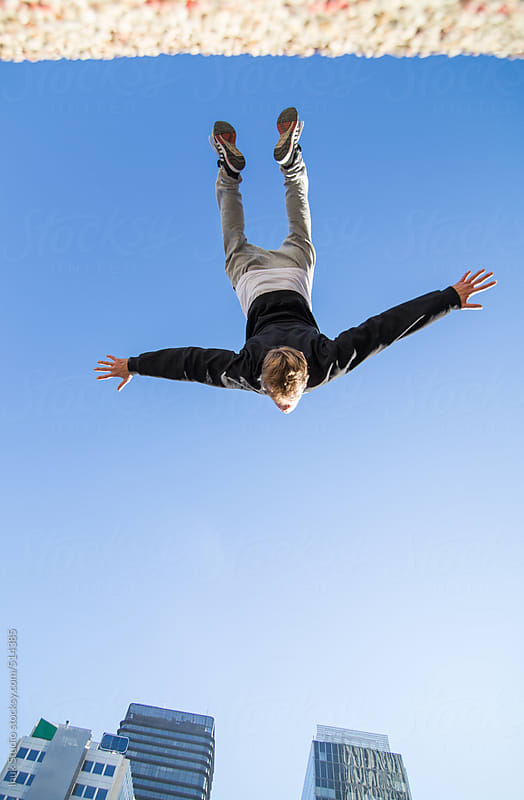 Nadir photography of a man doing a backflip in the air during a parkour training in a city by Inuk Studio for Stocksy United