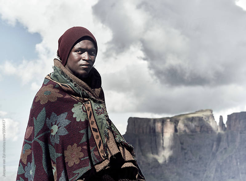 A  Portrait of a black Basotho shepherd wrapped in a traditional blanket against a story mountainous backdrop. by Jacques van Zyl for Stocksy United