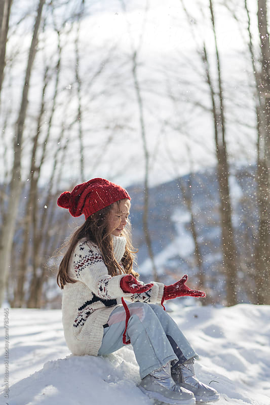 Girl playing in snow by Dejan Ristovski for Stocksy United