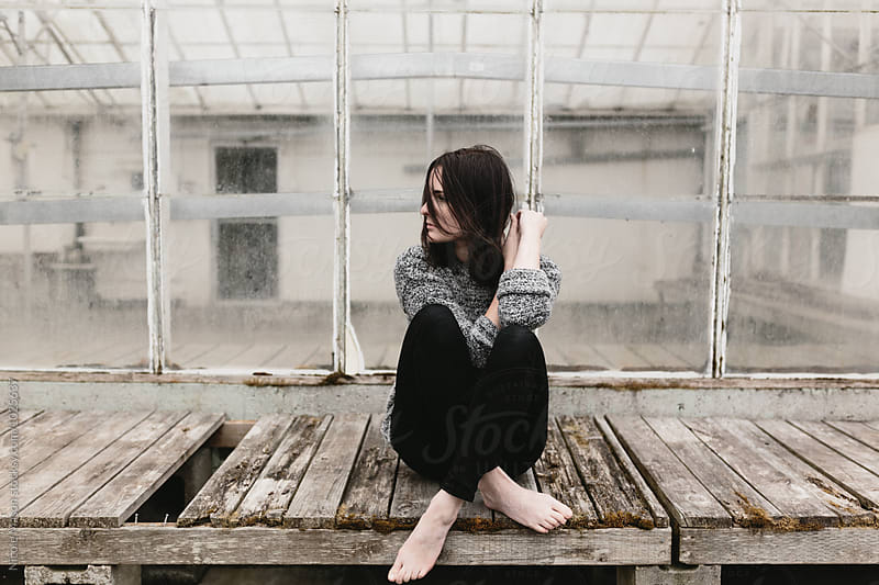 young woman sitting cross legged in front of old abandoned greenhouse by Nicole Mason for Stocksy United