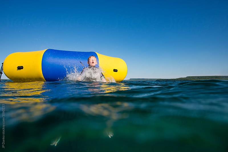 Splash of Little Boy Jumping Into Summer Lake From Water Trampoline At Cottage by JP Danko for Stocksy United