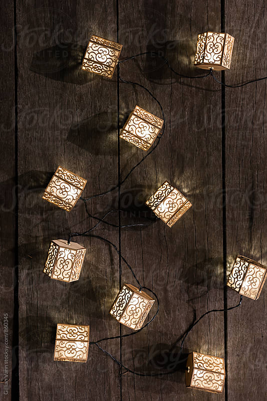 lantern solar powered lights on a wooden table at night by Gillian Vann for Stocksy United