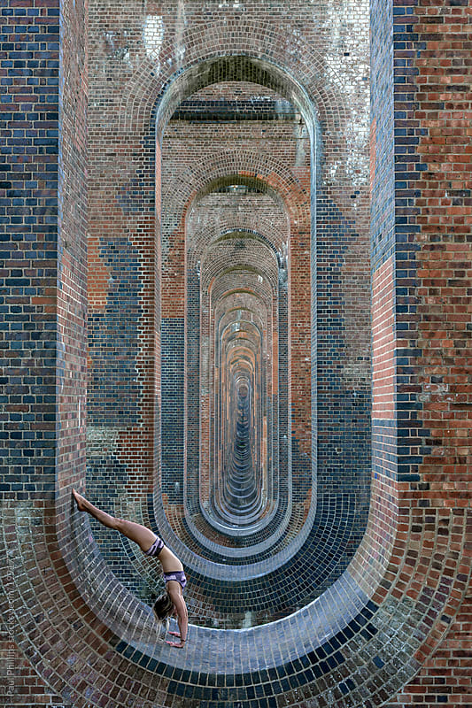 Female 20s performing a yoga back bend within the brick arches of a railway viaduct by Paul Phillips for Stocksy United