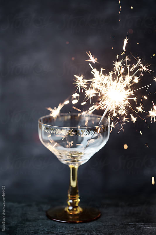 Champagne glass with a sparkler by Ruth Black for Stocksy United