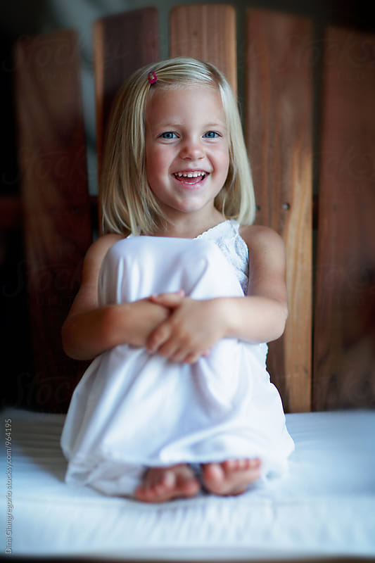 Little Girl Hugging knees in White Slip Dress by Dina Giangregorio for Stocksy United