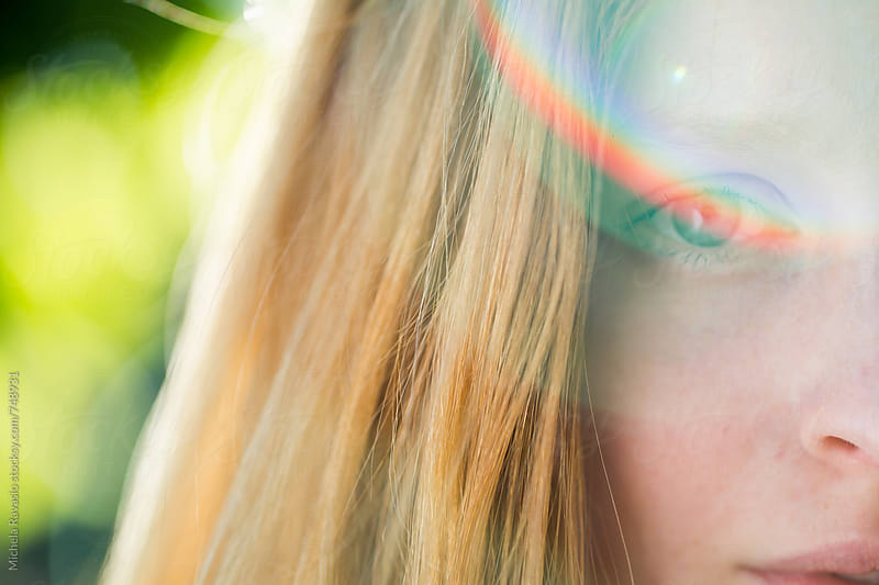 Close up of a girl with rainbow reflection on the eye by michela ravasio for Stocksy United