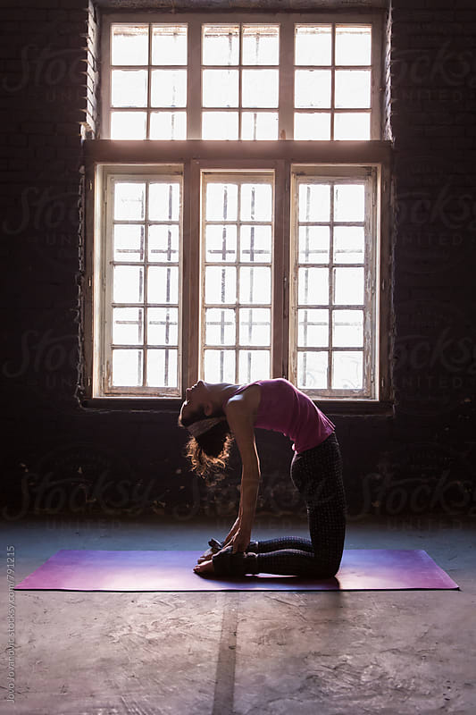 Full length of a young woman practicing yoga in Camel position on mat by Jovo Jovanovic for Stocksy United