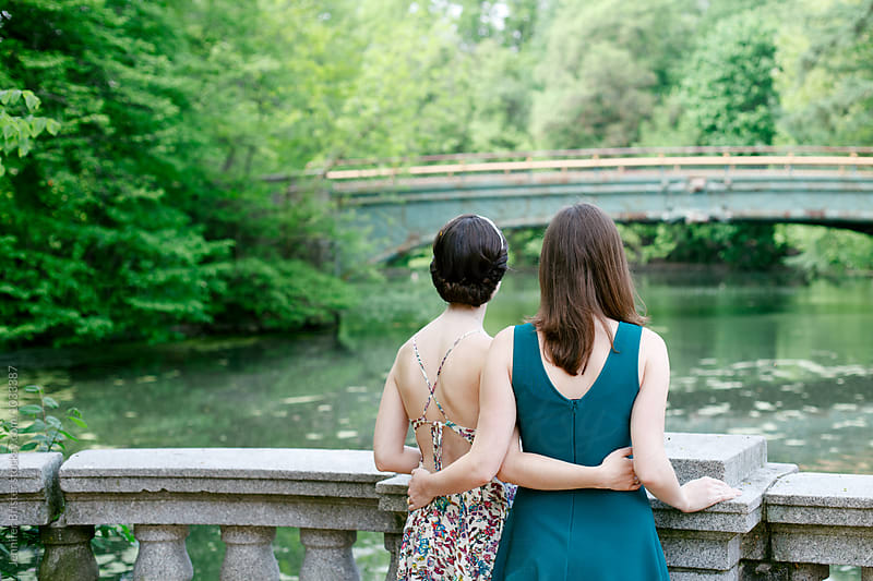 Two women holding each other and looking out at water by Jen Brister for Stocksy United