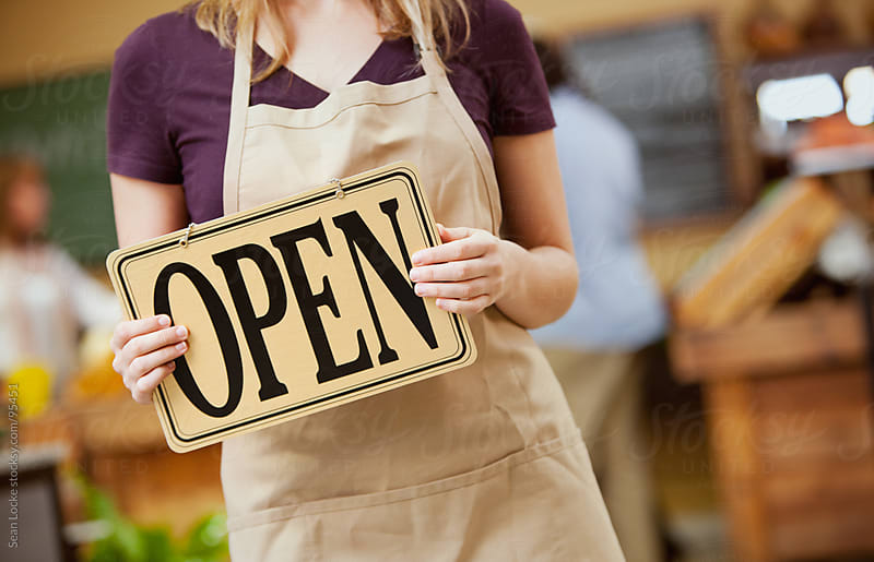 Market: Cashier Carrying Open Sign by Sean Locke for Stocksy United