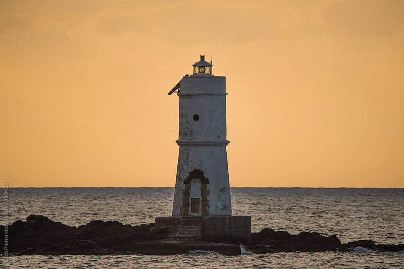 Lighthouse at sunset by Luca Pierro for Stocksy United