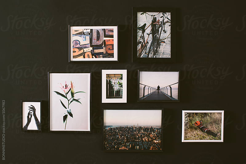 Variety of pictures hanging in a black wall.  by BONNINSTUDIO for Stocksy United