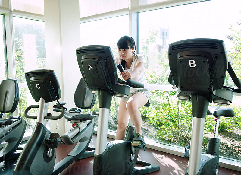 Asian woman exercising on a stationary bike. by W2 Photography for Stocksy United