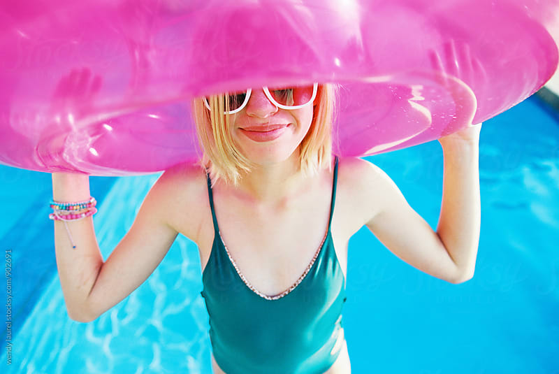 blonde girl in swimming pool wtih pink floaty by wendy laurel for Stocksy United