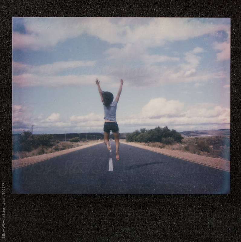 Polaroid film scan of a woman running and jumping on an empty highway by Micky Wiswedel for Stocksy United