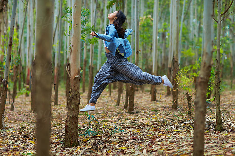 young woman jumping in the woods by Bo Bo for Stocksy United