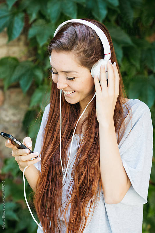 Beautiful freckled woman  listening music with headphones by Alberto Bogo for Stocksy United
