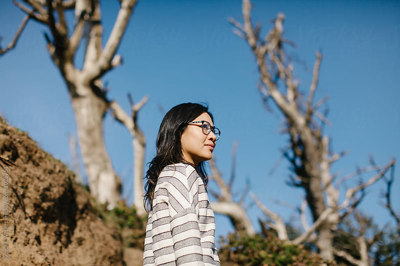 Trendy woman wearing glasses looking out by Kristine Weilert for Stocksy United