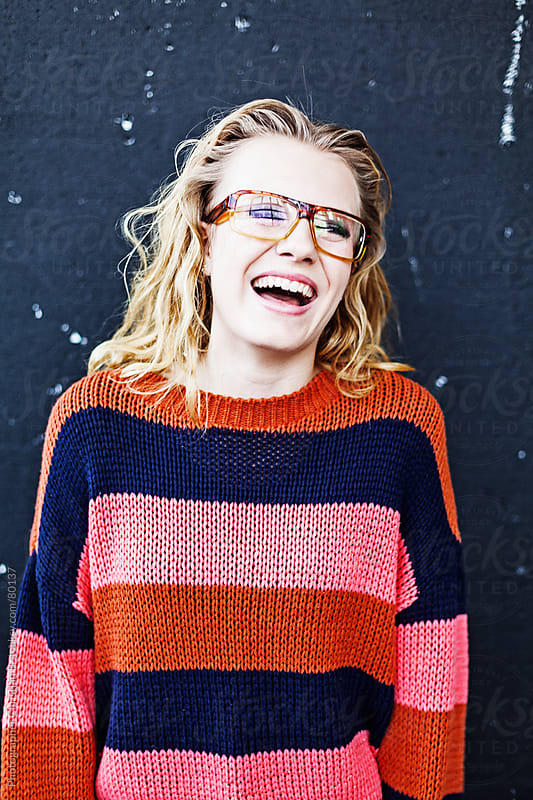 Young girl with glasses laughing by Photographer Christian B for Stocksy United