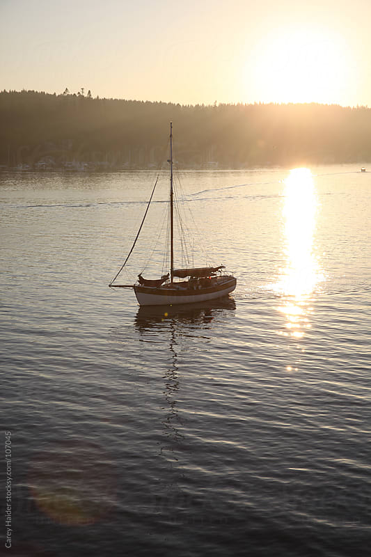 A Lonely Boat Sailing In The Water At Sunset by Carey Haider for Stocksy United