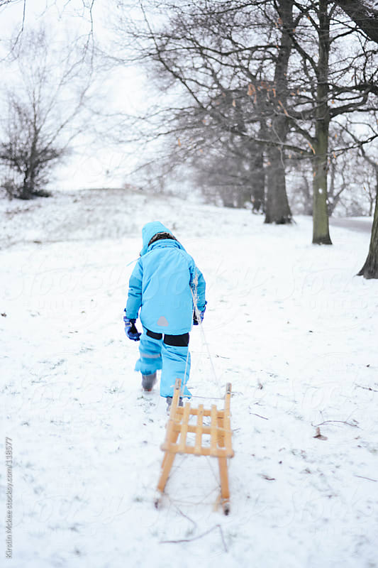 Boy walking up a snowy hill with a wooden sledge by Kirstin Mckee for Stocksy United