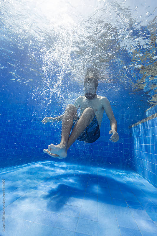 Man underwater in the pool after a jump by Jovana Milanko for Stocksy United