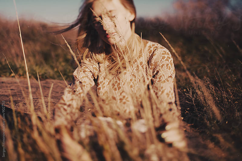 Young girl touches a grass in field by Sergey Filimonov for Stocksy United
