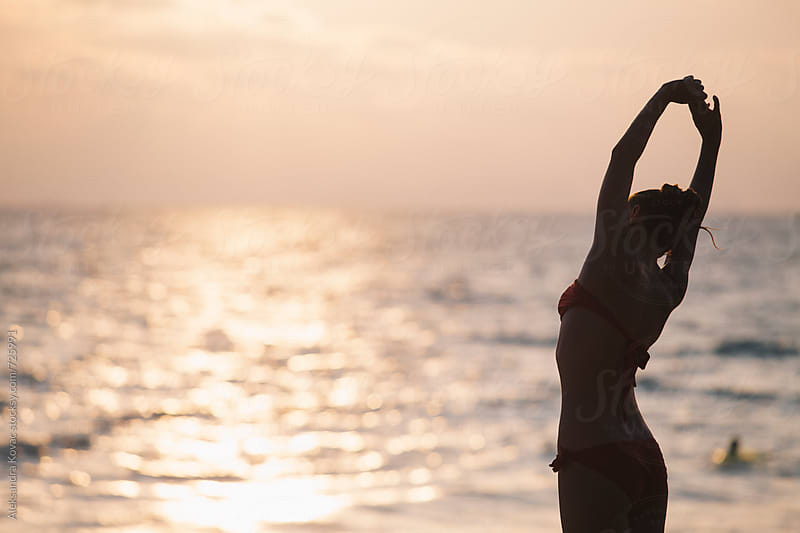 Woman stretching on the beach at sunset by Aleksandra Kovac for Stocksy United