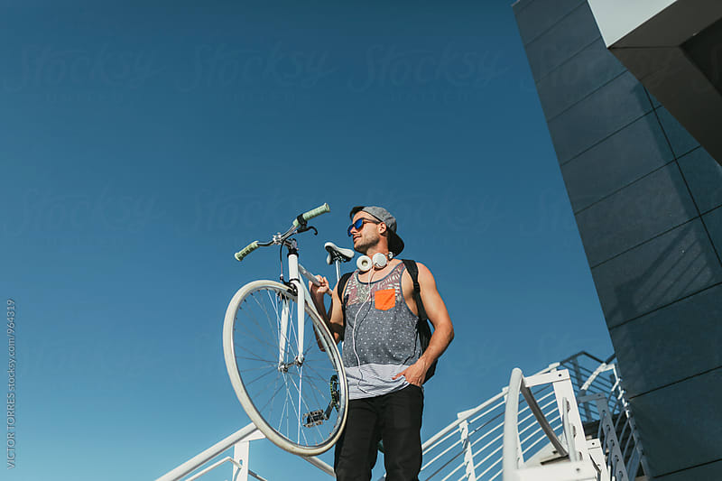 Young Man Carrying His Bicycle Against a Blue Sky