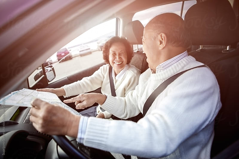 Happy traveling senior Asian couple looking at a map inside a car by Suprijono Suharjoto for Stocksy United