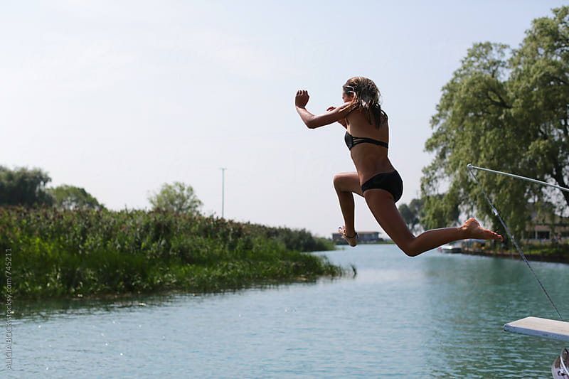 A Girl Jumping Off A Diving Board Into A Lake On A Summer Day by ALICIA BOCK for Stocksy United