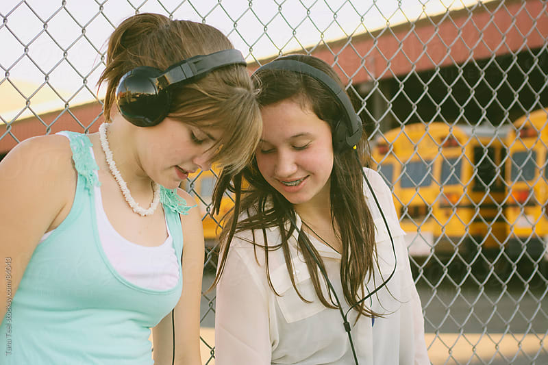 Students stopping to listen to music before getting on the school bus by Tana Teel for Stocksy United