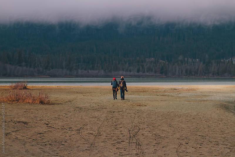 Couple walks on northwest beach by Jesse Morrow for Stocksy United