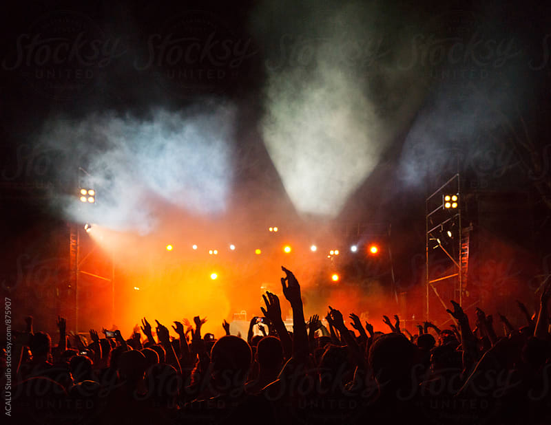 Silhouette of young people at a concert in the evening by ACALU Studio for Stocksy United