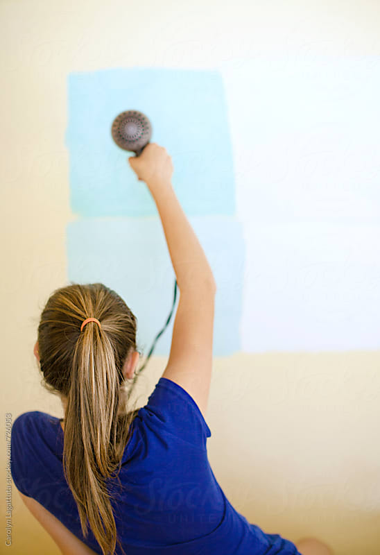 Teenage girl using a hair dryer to dry paint samples in her bedroom by Carolyn Lagattuta for Stocksy United