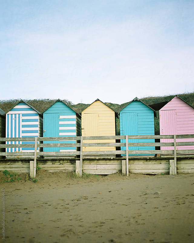colourful painted beach huts by Suzi Marshall for Stocksy United