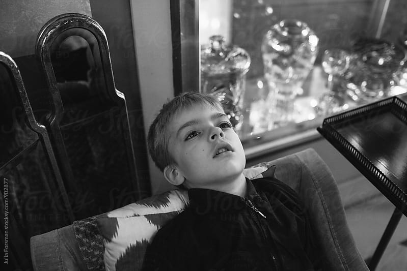 Boy leans back on chair in a room with old fashioned objects. by Julia Forsman for Stocksy United