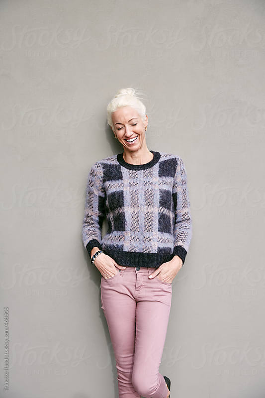 Portrait of mature woman with blonde hair against grey wall by Trinette Reed for Stocksy United